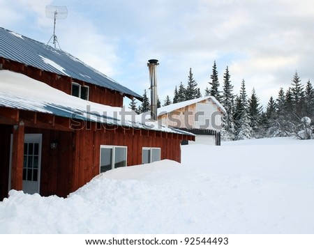 Snow piled up around house covering windows after an Alaskan storm.