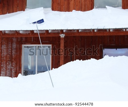 Snow piled up on a roof in winter with a snow shovel and large piles on the ground.