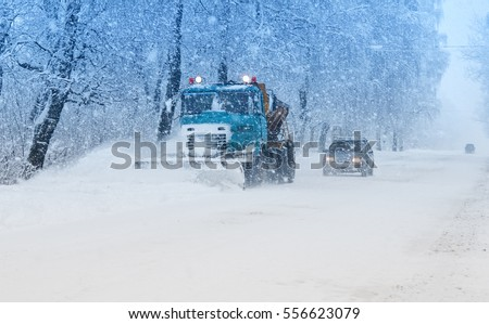 snow plow doing snow removal during blizzard #556623079