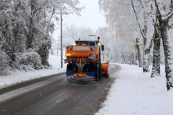 Snow plow is sprincling salt or de-icing chemicals on pavement in city.