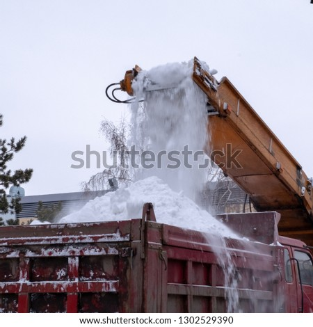 Snow plow tractor and truck work on the street. Snowplow cleans the city after a snow storm. Close-up. Municipal urban road maintenance. Winter season. Square picture.