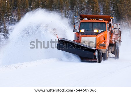 Snow plow truck clearing road after winter snowstorm blizzard for vehicle access #644609866