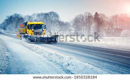 Snow plow truck clearing snowy road. Snowblower truck plowing snow on the driveway after snowstorm. Foto stock ©
