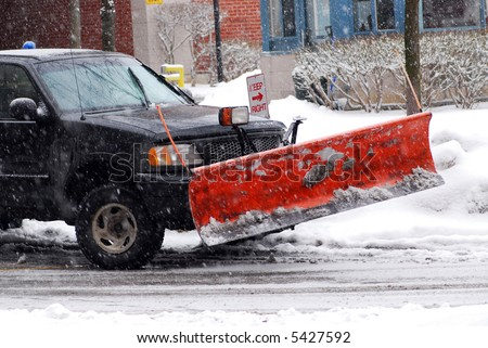 Snow plow truck on a road during a snowstorm #5427592