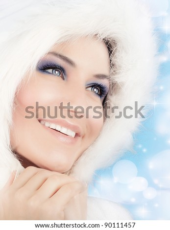 Snow queen, beautiful woman in Christmas style makeup, female portrait over blue holiday background with shiny glowing glitters and bokeh lights