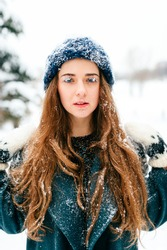 Snow queen. Young girl with amazing beautiful face, blue fantsastic eyes and long perfect hair closeup portrait outdoor. Freezing skin. Eyelashes and lips covered with snow. Fairy fantasy unusual lady
