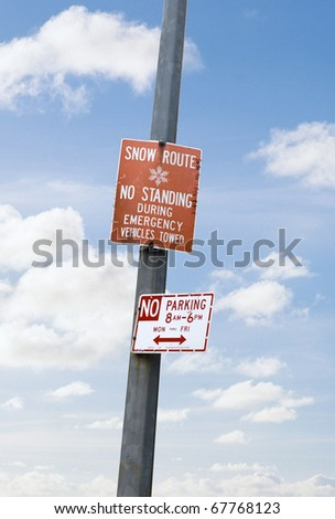 snow route sign and no parking sign mounted on the column against the blue sky