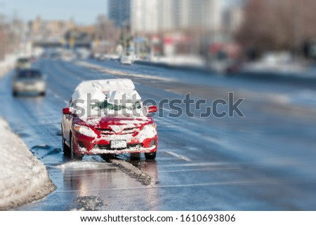 snow shifts onto a car's windshield as it stops at a red light in winter - driving blind