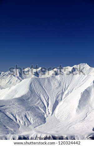 Snow slope in high mountains. Caucasus Mountains, Georgia, view from ski resort Gudauri.
