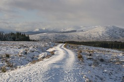 Snow snake path through white valley, mountains in a sunny day. Contrast and shiny day in the snow. Solo adventure