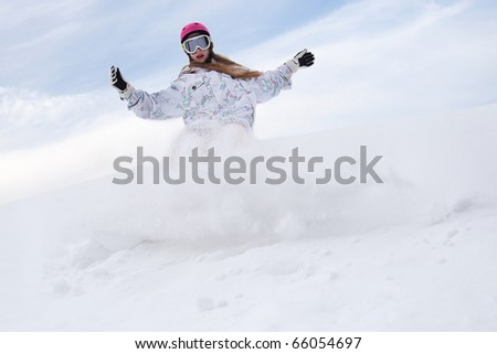 Snow splashes from girl rider snowboard
