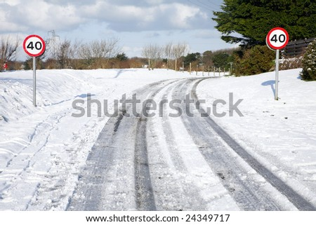 Snow tracks on a country road and 40 mph signs.