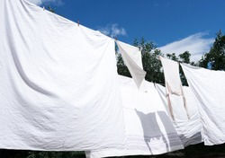Snow-white clean sheets hang on a rope and dry outdoors