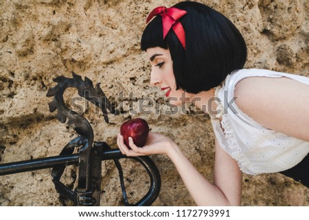 Snow White handles an apple to a iron figure of a dragon.
