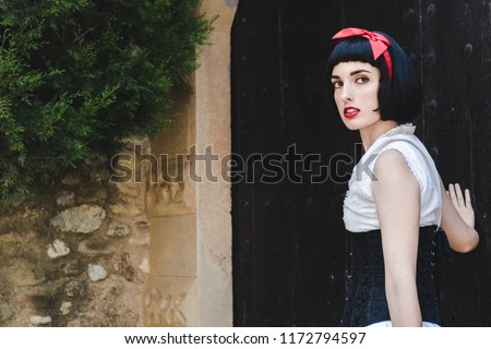 Snow White is looking to his left, with her hand on the door.