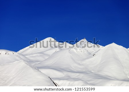 Snow-white mountains and blue sky. Caucasus Mountains, Georgia, view from ski resort Gudauri.