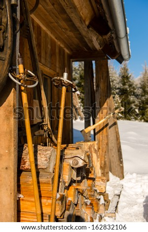 Snow winter cottage from outside ski poles, logs of wood