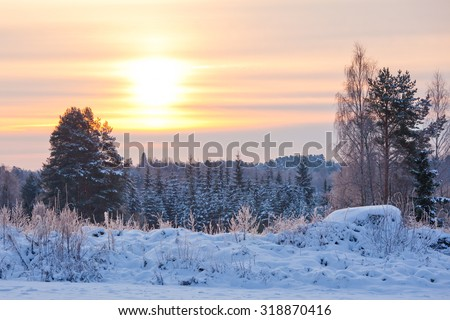 Snow winter landscape and sun shining behind clouds