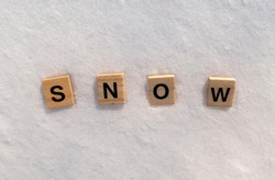 Snow word on a white clean snow. Snow is written on a snow with wooden letters.