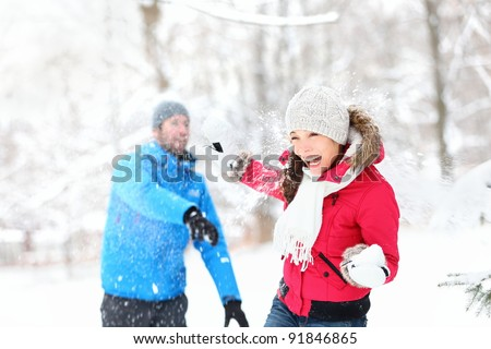 Snowball fight. Winter couple having fun playing in snow outdoors. Young joyful happy multi-racial couple.