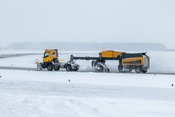 Snowblower cleans airport taxiway in a blizzard