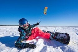 snowboard and people in bright clothes lying in the snow on a snowboard and kite controls. Deep blue sky and sun in the background