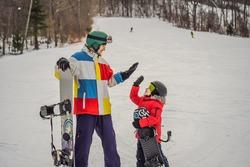 Snowboard instructor teaches a boy to snowboarding. Activities for children in winter. Children's winter sport. Lifestyle