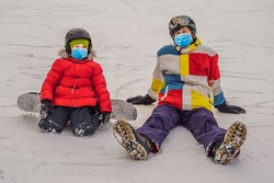 Snowboard instructor teaches a boy to snowboarding wearing a medical mask during COVID-19 coronavirus. Activities for children in winter. Children's winter sport. Lifestyle