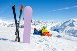 snowboarder and skiier sitting on snow and see at mountains