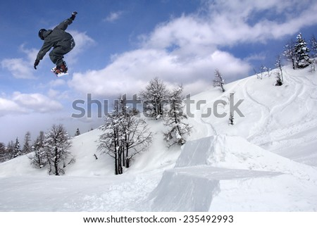 Snowboarder at extreme jump in high mountains at sunny day #235492993