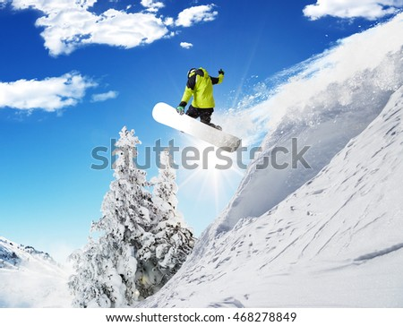 Snowboarder at jump in Alpine mountains in beautiful sunny day. Copy-space for text