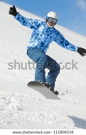 Snowboarder balances when flies in jump on snowboard over snowy ski slope.