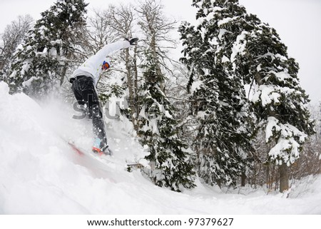 Snowboarder doing a jump and free ride on  powder snow at winter season
