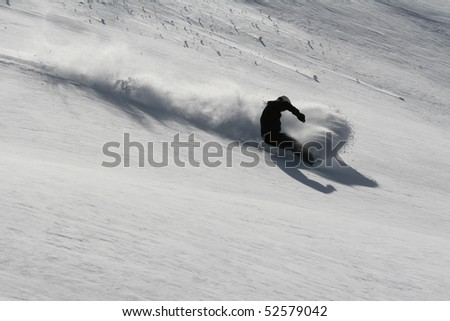 snowboarder doing a powder turn in deep snow - stock photo