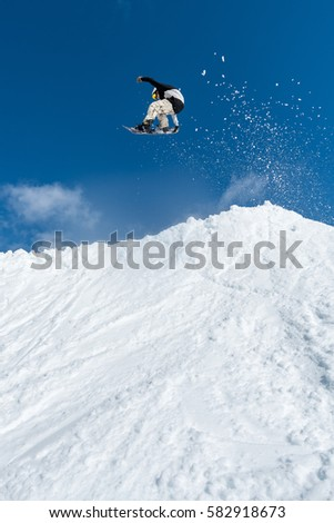 Snowboarder executing a radical jump against blue sky. #582918673