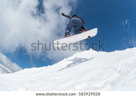 Snowboarder executing a radical jump against blue sky. #583929028