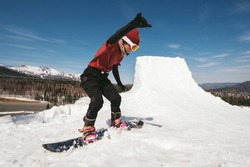 Snowboarder female jumping on quarter pipe snowboard in winter sunny day. Freestyle snowboard training