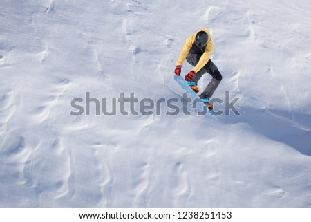 Snowboarder flying on the background of snowy slope. Extreme winter sports, snowboarding. #1238251453