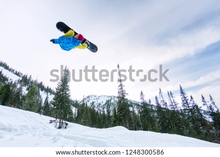 Snowboarder freerider jumping from a snow ramp in the sun on a background of forest and mountains #1248300586