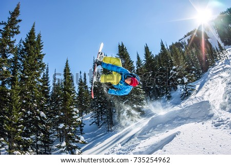 Snowboarder freerider jumping from a snow ramp in the sun on a background of forest and mountains. #735254962