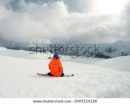 snowboarder girl sitting on snowboard, snow mountain, sky clouds #1049224328