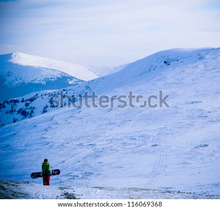 Snowboarder girl traveler in wonderful winter mountains