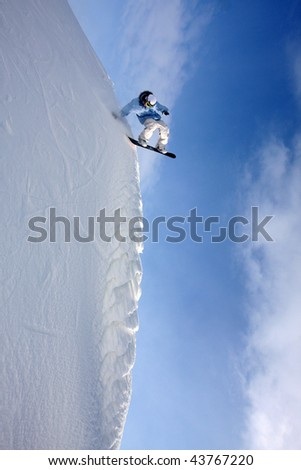 snowboarder goes downwards on a steep wall