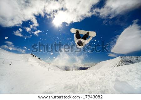 Snowboarder going off jump doing a backflip