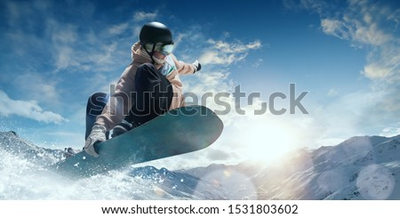 Photo of  Snowboarder in action. Extreme winter sports.
