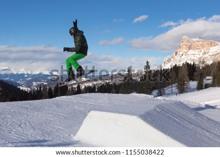 Snowboarder in Action: Jumping in the Mountain Snowpark. #1155038422