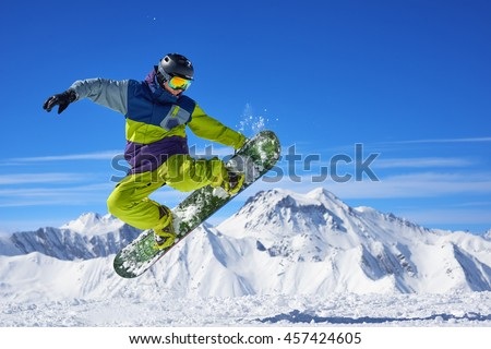 Snowboarder in bright sportswear doing trick against of beautiful mountains Stock fotó ©