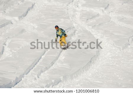 Snowboarder in orange sportswear riding down a snow hill on bright winter day against the white snow #1201006810