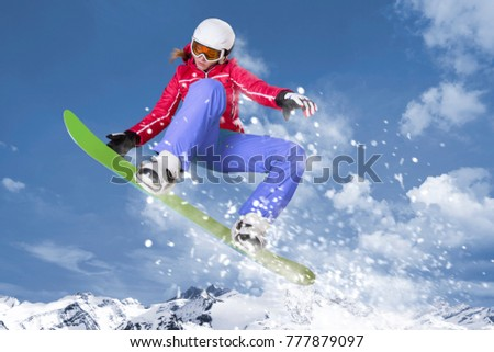 Snowboarder in red jacket and lilac trousers jumps on her green snowboard through the air in front of a mountain panorama and winter landscape #777879097
