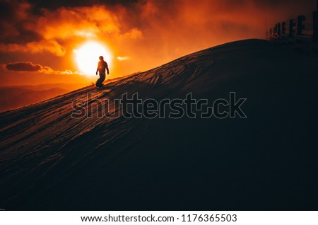Snowboarder in ski resort. Winter sport photo. Orange sunset light in background. Edit space. Christmas and New Year time, snowy photo, edit space #1176365503